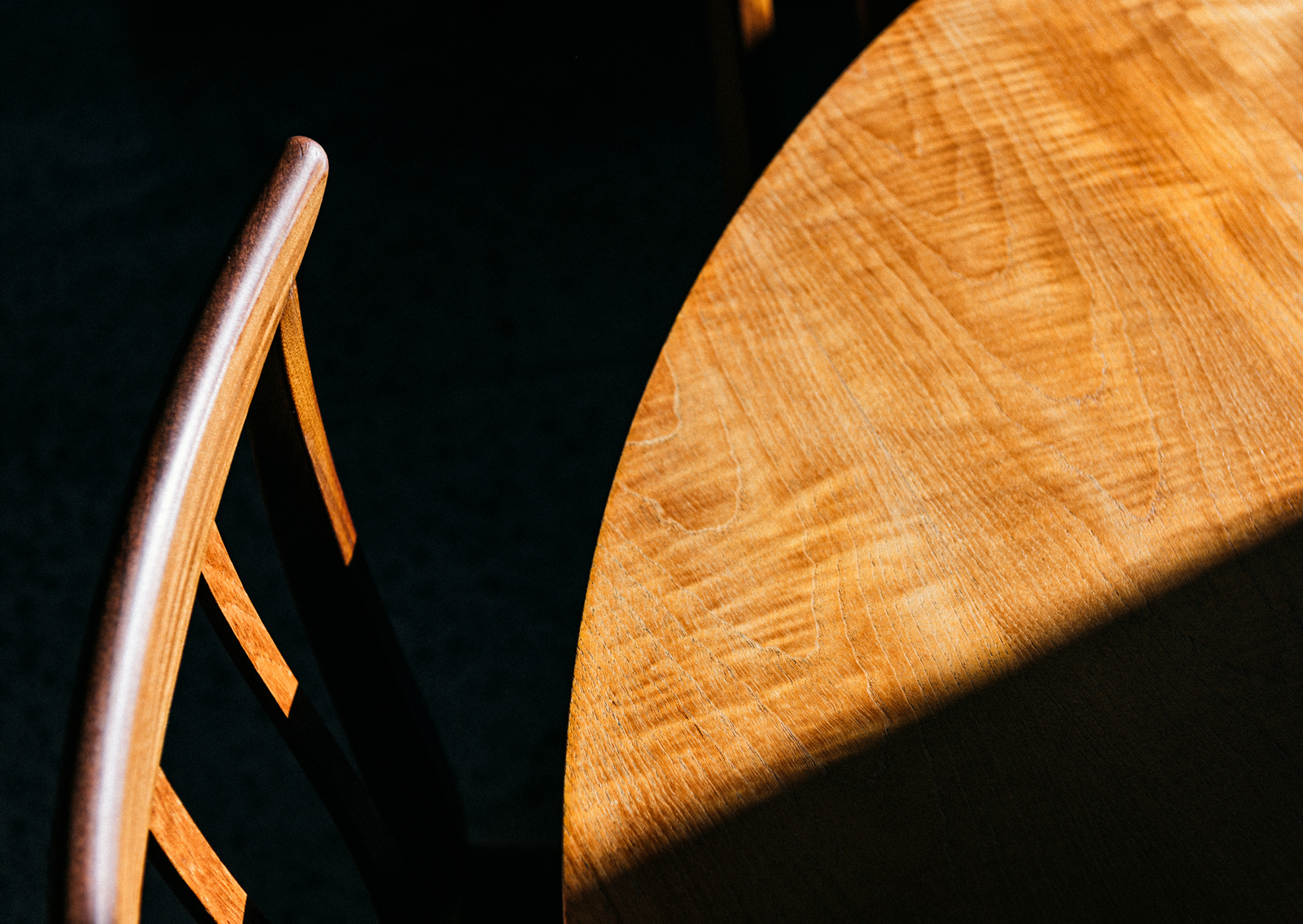 Keith and Sandy branding – dramatic close up of warm toned wooden table and chair