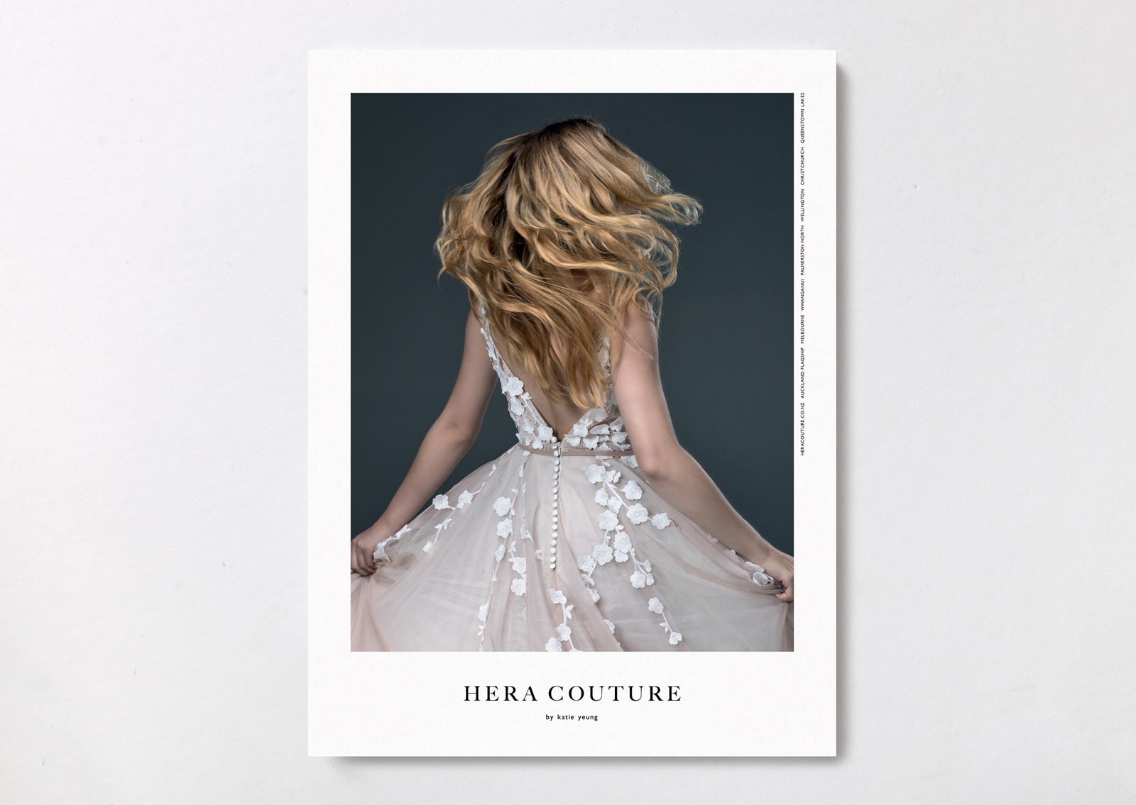 Hera Couture brand postcard – shows flowing hair of bride from behind and detail of gown with cascading flowers