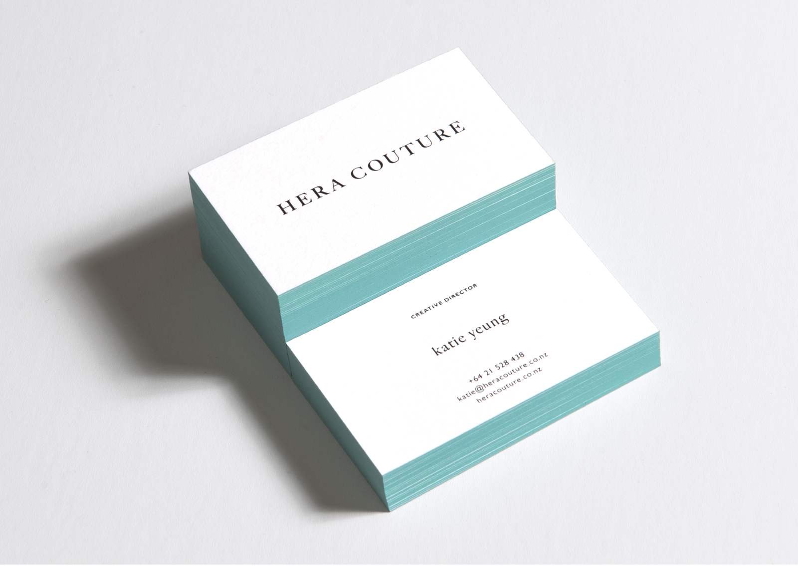 Hera Couture letterpress business cards in stacks highlight aqua painted edges and black foil type