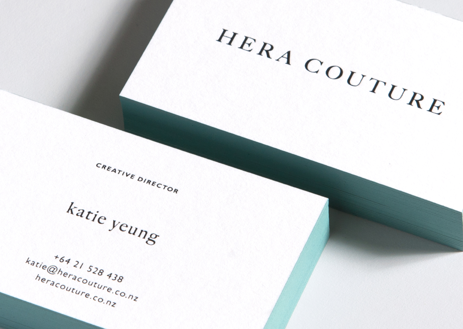 Hera Couture letterpress business cards have aqua painted edges and black foil type