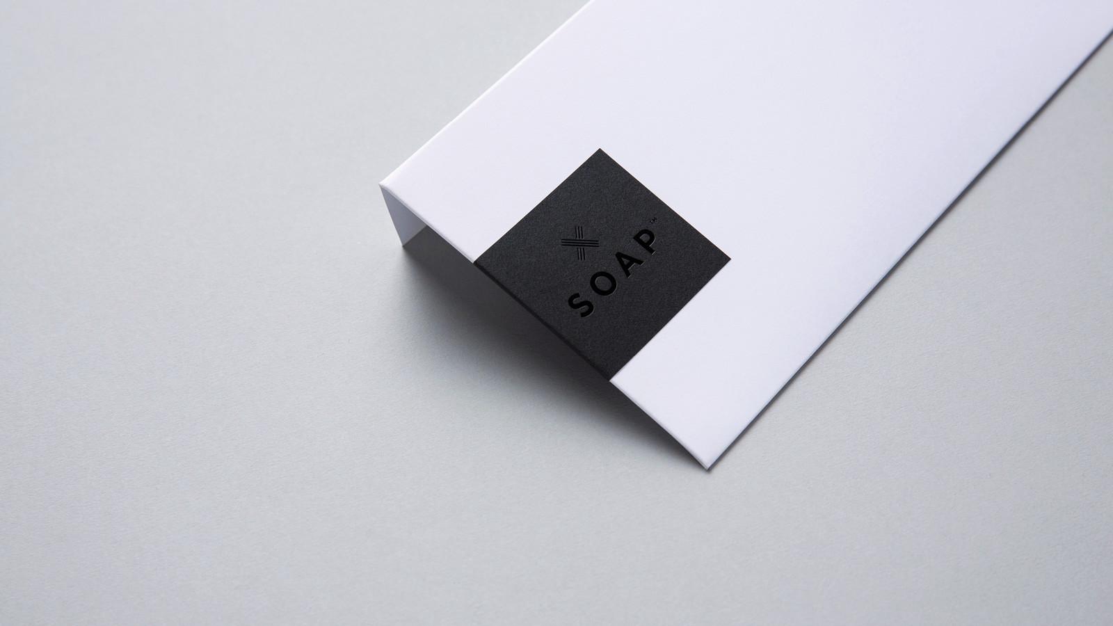 SOAP™ black foil branded sticker on white envelope