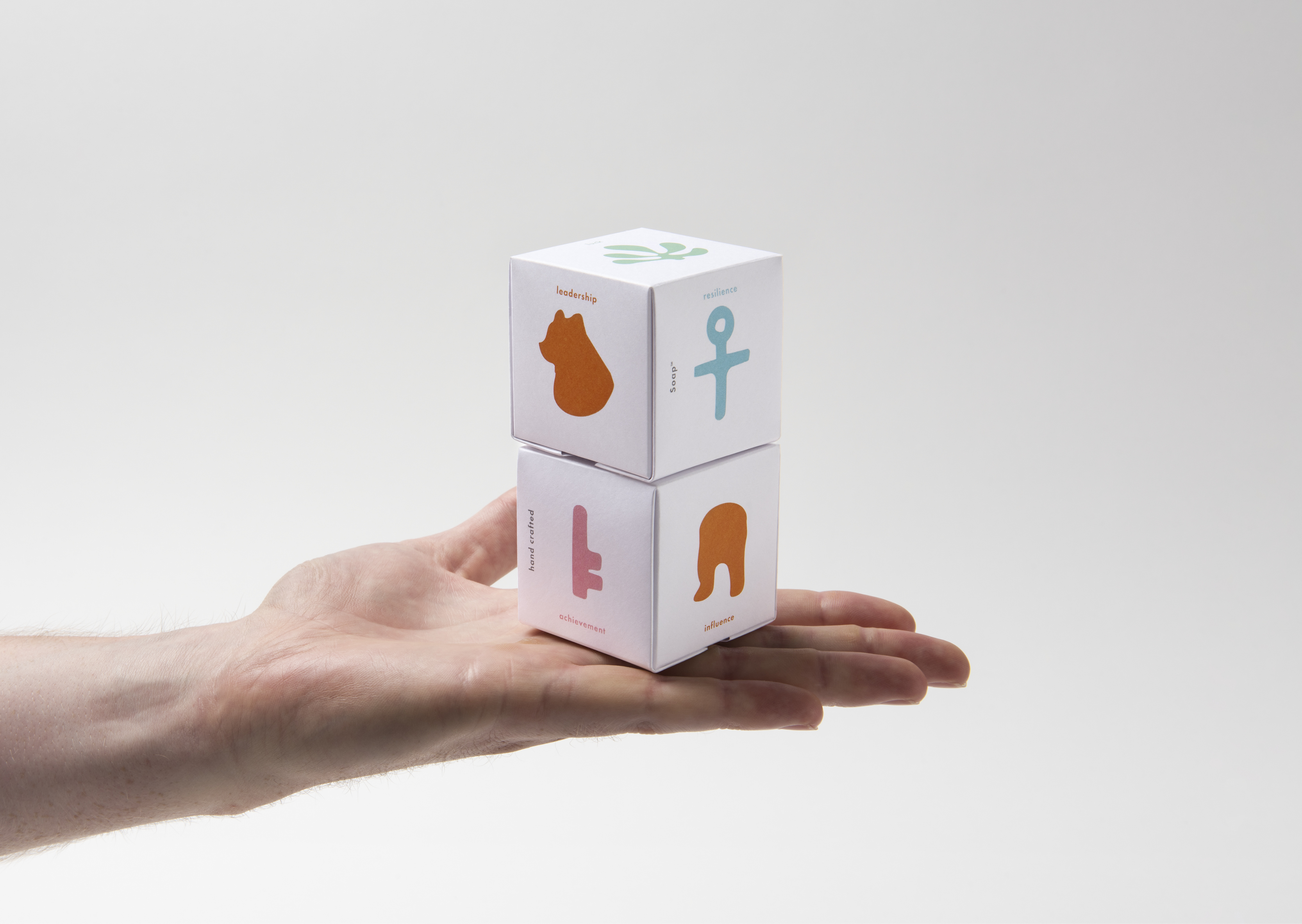 Two stack of beautifully illustrated soap packaging in palm of hand