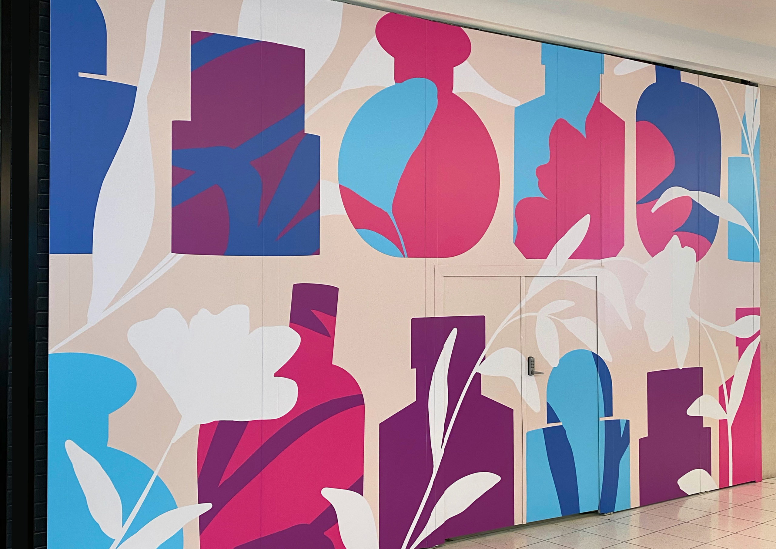 Large scale retail graphics at Sylvia Park Level 1 Launch featuring illustrated oversized perfume bottles overlayed with pink, purple and blue blooms