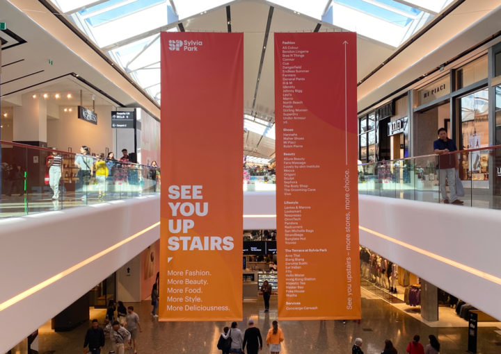 Large scale hanging Banners designed to capture shoppers' attention to drive foot traffic to new Level 1 retail at Sylvia Park , New Zealand's largest shopping mall