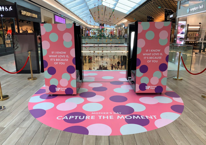 Two playfully coloured photo booths and curving floor decal 'Capture the moment' at Sylvia Park Shopping Centre retail activation