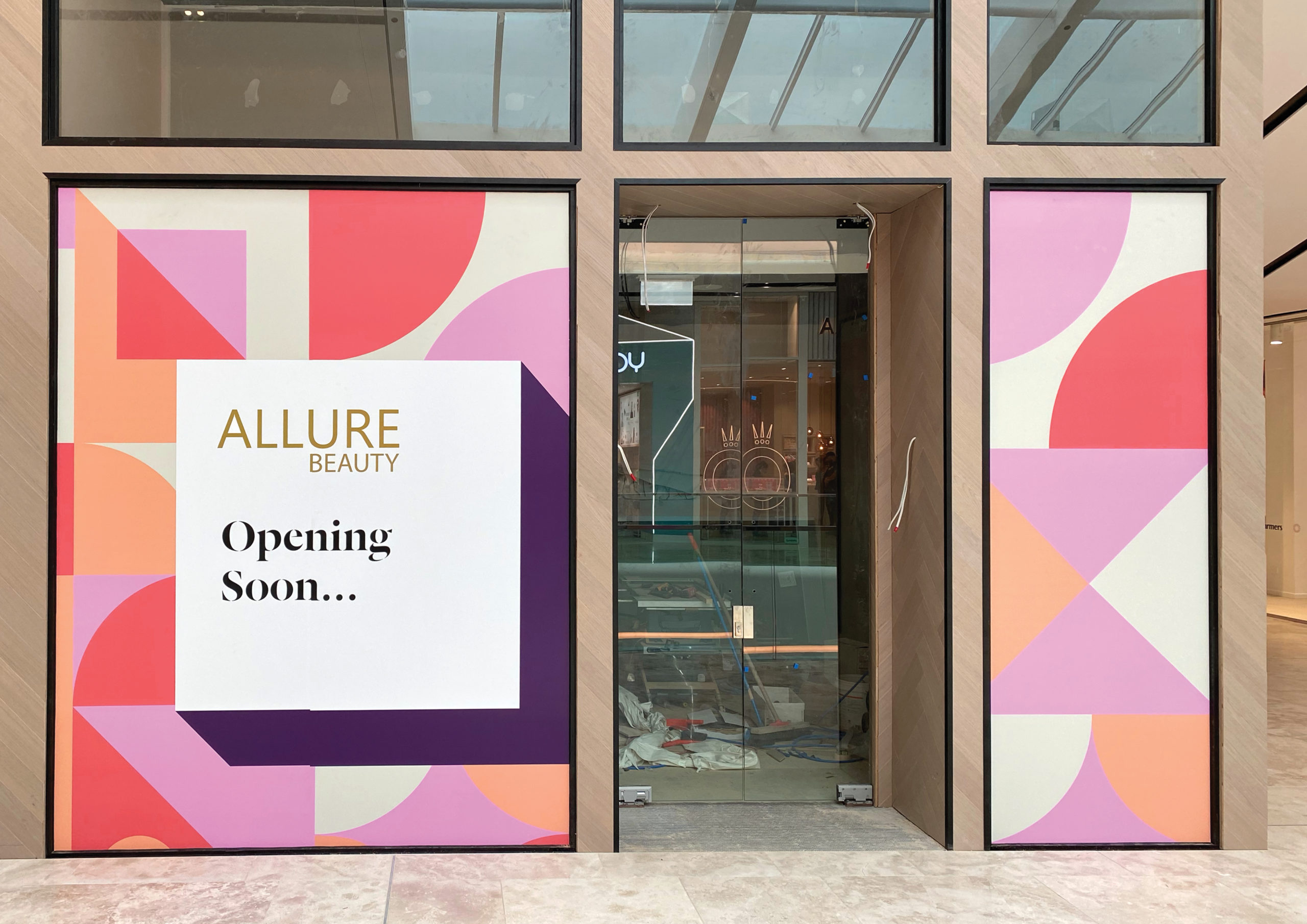 Sherbet coloured geometric pattern of circles, squares and triangles with Opening Soon message overlayed on store windows during Fit out